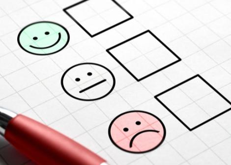 Bilde av 3 smileys og 3 avkryssningsbokser. Smileyene er blid, nøytral og sur. Det skimtes en penn på bildet.